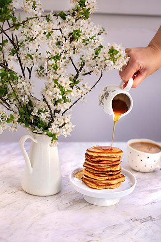 Woman drizzling maple syrup on a stack of pancakes