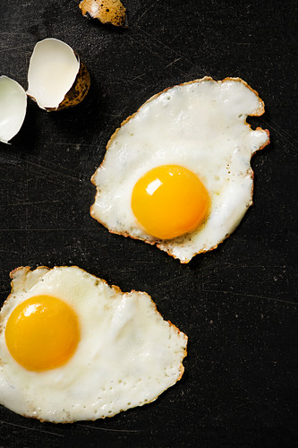 Two fried quail eggs on black cooktop surface with cracked egg shells to the side.
