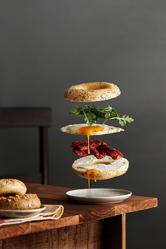 A bagel breakfast sandwich with ingredients floating. Rustic wood table setting against a gray wall.