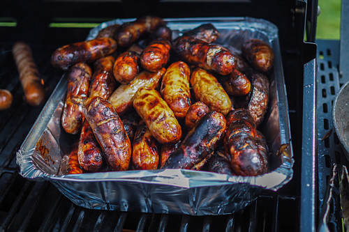 Sausages in an aluminium tray on a gas grill