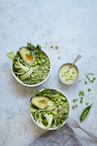 Green bowls with broccoli 'rice', avocado, edamame and pea dressing