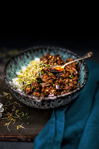 Crispy beef stir fry with aubergine and mushrooms served in a bowl over rice and spicy chilli sauce