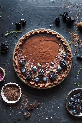 Chocolate tart topped with blackberries and blueberries on a vintage pie plate