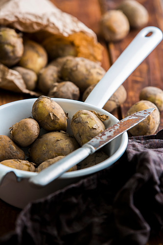 New potatoes in a sieve with a knife