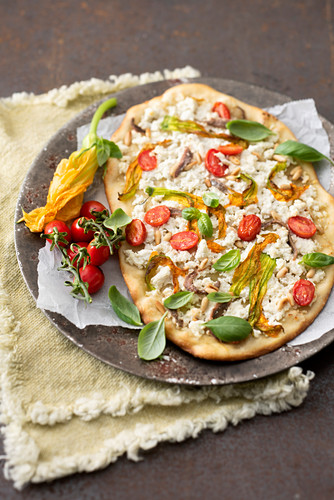 Pizza topped with ricotta, courgette flowers, pine nuts, anchovies and cherry tomatoes