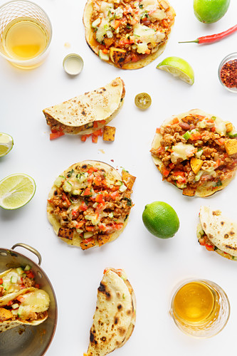 Mexican tacos with chili con carne, grilled sweet potatoes and grated cheese on white background