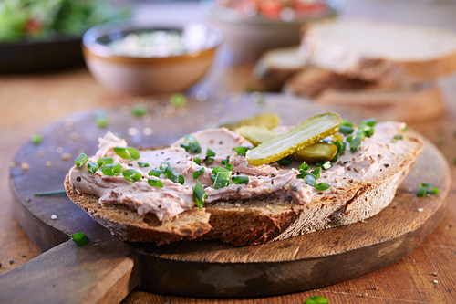 A slice of bread spread with liver pâté and topped with chives and gherkins