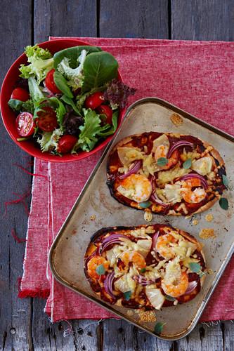 Mini-Pizza mit Garnelen und Ananas auf Ofenblech (Aufsicht)