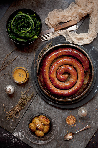 A Cumberland Sauagew with Hasselback Potatoes Mustard Sauce and Cavalo Nero