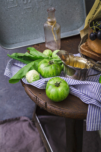 An arrangement of green tomatoes and Brussels sprouts on a wooden stool
