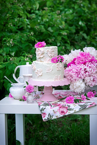 Buttercream cake with peonies in a garden
