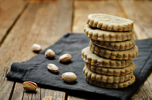 Cashew butter cookies with pistachios on a wood background