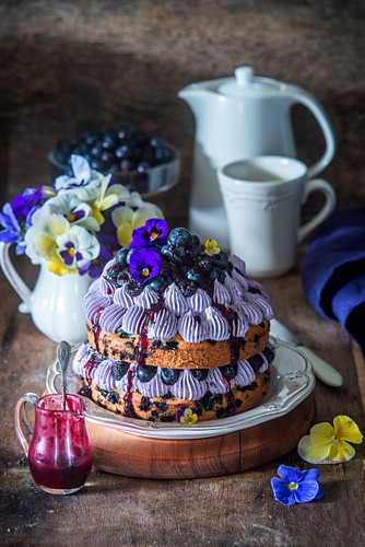 Festive berry cake with edible flowers