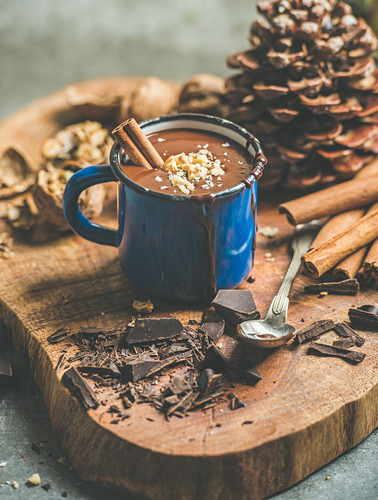 Rich winter hot chocolate with cinnamon sticks and walnuts