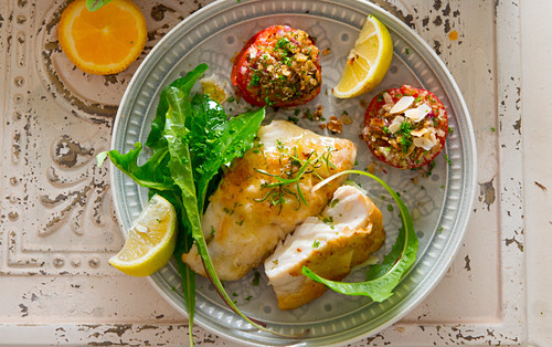 Mediterranean coalfish served with stuffed tomatoes and a dandelion salad