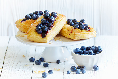 Puff pastry tartlets with blueberries on a cake stand