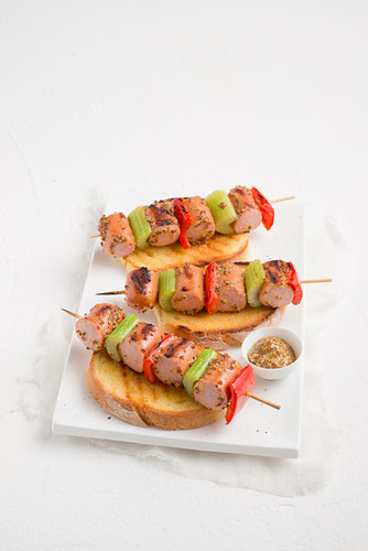 Marinated sausage skewers with vegetables on toast