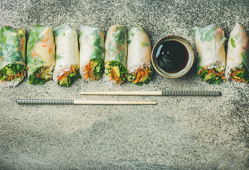 Vegan spring or summer rice paper rolls with vegetables, sauce and chopsticks