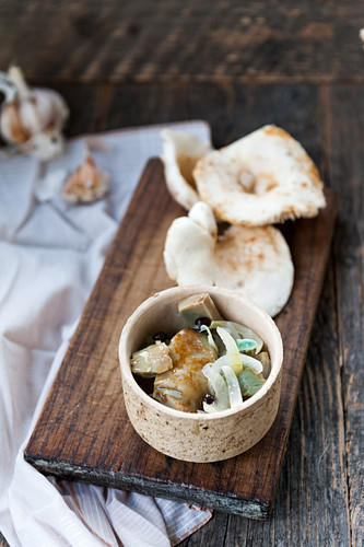 Pickled Lactarius piperatus mushrooms with onion, pepper and garlic