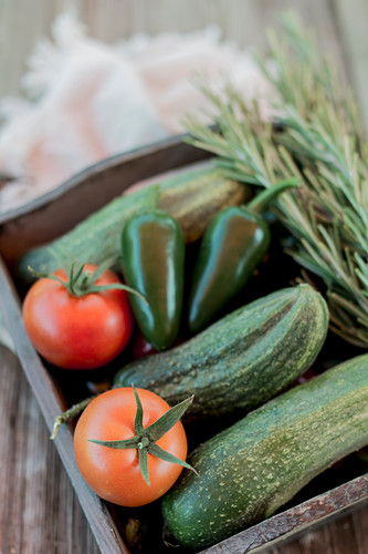 Garden vegetables and rosemary in a wooden box