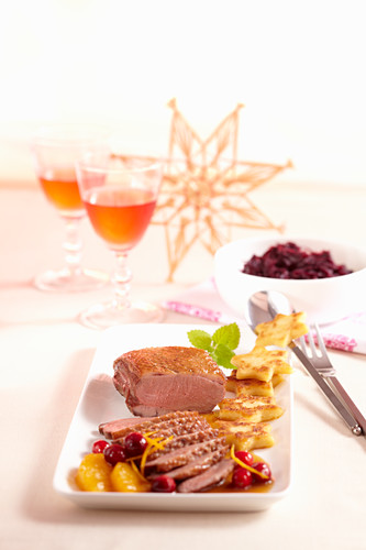 Rare duck breast with a fruity orange and cranberry sauce, fried potato stats and red cabbage