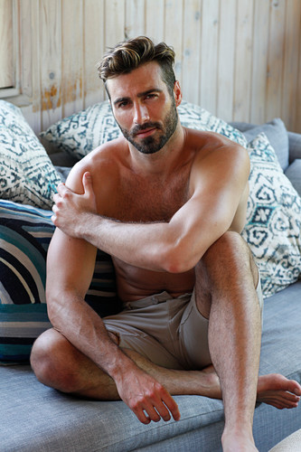 A young topless man sitting on a sofa wearing shorts