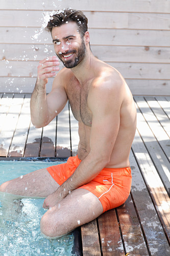 A young topless man sitting by a pool wearing shorts