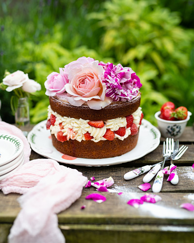 Strawberry cake with cream and roses on a garden table