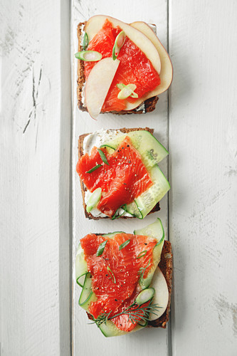 Danish traditional snack smorrebrod with salmon, cucumbers and cream cheese