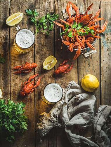 Two pints of wheat beer and boiled crayfish with lemon and parsley over old wooden rustic background