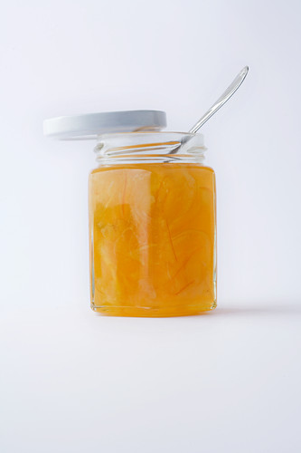 A jar of tangerine jam against a white background