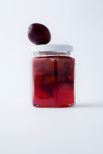 A glass of plum jam against a white background