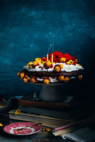 A merengue with candles and smoke, with eatable flowers, whipped cream and cholate