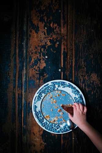 Oce piece of chocolate cake on a brocante plate with a little child hand