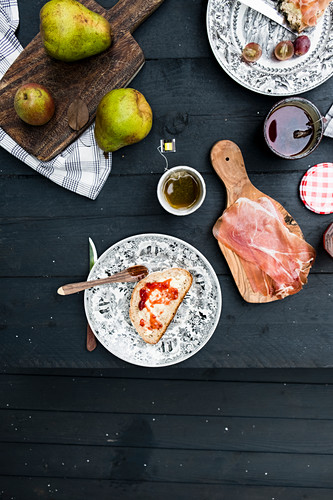 A slice of bread with marmelade, a cup of tea, pears from above on a black wooden table