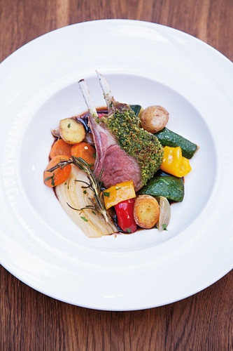 A rack of lamb with a herb crust and potato peperonata