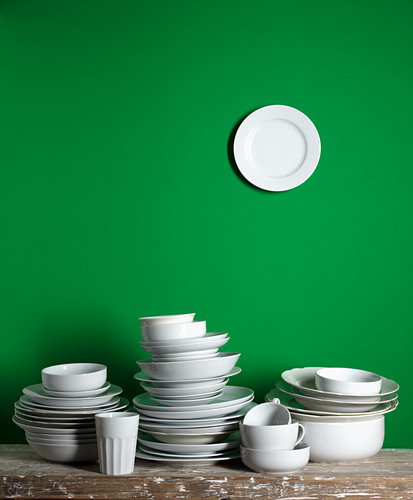 Stacked white dishes in front of green wall, with a dish hung on the wall