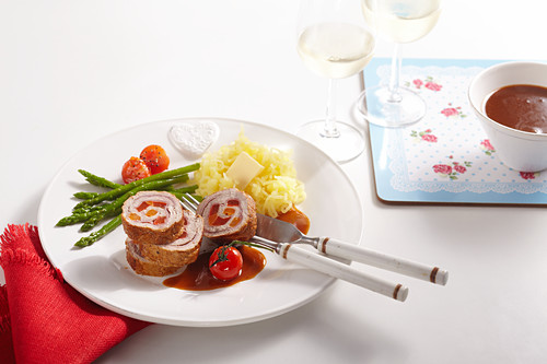 Veal roulade filled with vegetables, green asparagus, cherry tomatoes, mashed potatoes and gravy