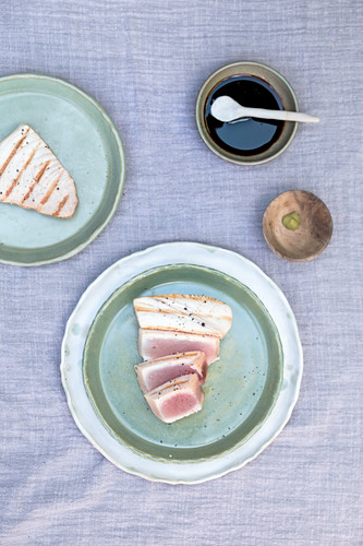 Grilled tuna from the bbq on green plates with a little bowl of soya sauce and wasabi on a linen cloth