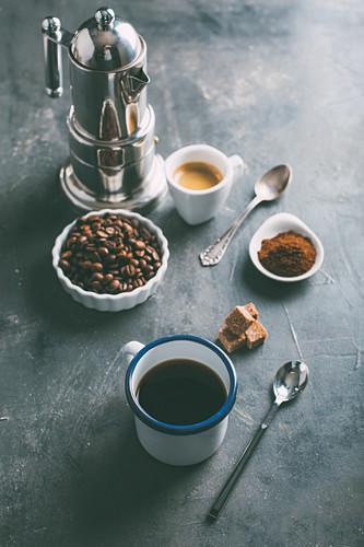 Kaffeebohnen und Kaffeepulver sowie schwarzer Kaffee und Espresso in Tassen