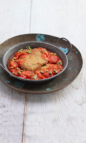 Breaded escalope in a tomato and caper sauce