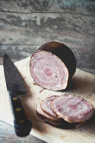 A a sliced French Andouille de Guéméné tripe sausage on a wooden board with a vintage Sabatier knife