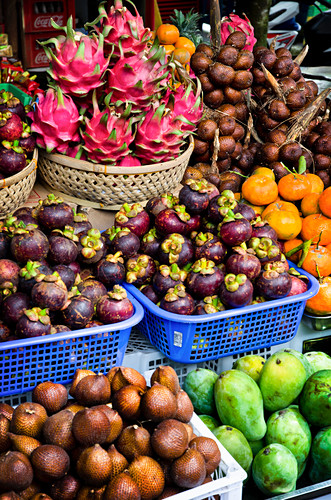 A close up of a fruit stand in Bali, Indonesia with baskets of Snakefruit, Dragon fruit, Mangostene, Papaya and Balinese bitter oranges