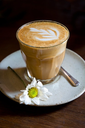 A cafe Latté in a Duralex Picardie tumbler glass with a white daisy on the side