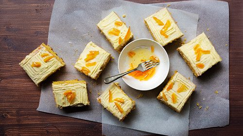 Pieces of orange and poppy seed cake with a bowl of candied peel