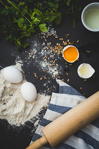 An arrangement of ingredients and utensils: eggs, flour, herbs, pine nuts and a rolling pin