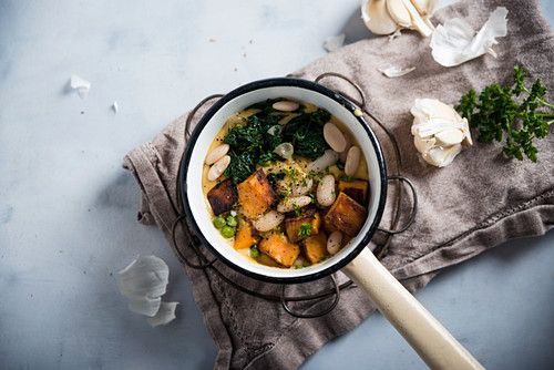 Vegan stew with roasted sweet potatoes, white beans, peas and spinach