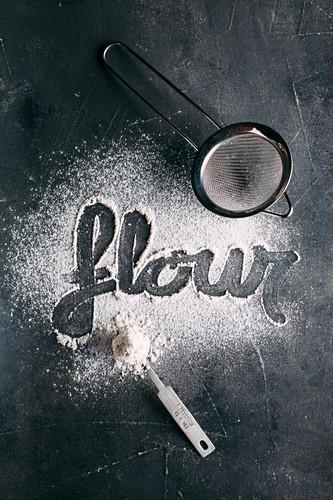 Mehl mit Schriftzug 'flour' und Sieb auf dunklem Hintergrund