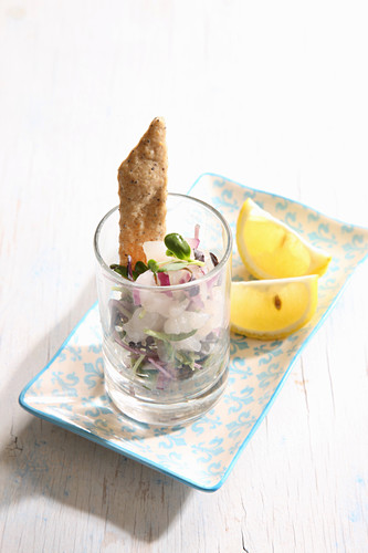 Ceviche served in a glass with crackers and lemon wedges