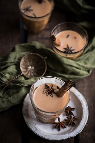 Mehrere Gläser Chai-Tee mit Sternanis und Zimtstangen